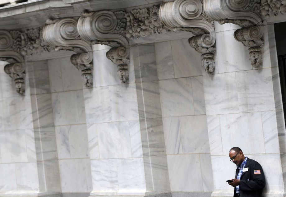 FILE - In this Monday, Aug. 24, 2015, file photo, a trader looks at his phone outside the New York Stock Exchange, as world stock markets plunged after China's main index sank to its biggest drop since the early days of the global financial crisis. The slide on Wall Street could damage public-employee pension funds around the country that have yet to recover from the Great Recession. Since the start of 2016, stocks have been down by about 8 percent. Photo: Seth Wenig, AP / AP