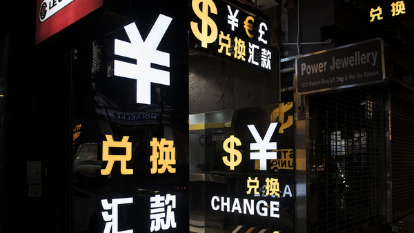 Currency symbols are illuminated at a currency exchange store at night in the Mong Kok district of Hong Kong, China, on Saturday, Oct. 24, 2015. The Hong Kong Monetary Authority bought the most U.S. dollars in six years in October to keep its currency within the permitted trading band amid inflows into its stock market and signs the city will be forced to raise interest rates. Photographer: Xaume Olleros/Bloomberg