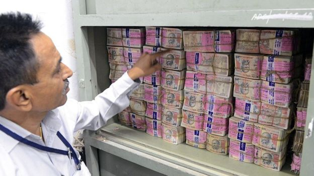 An Indian bank employee looks at deposited old denomination 1000 Rupee currency notes in a bank vault in Ahmedabad