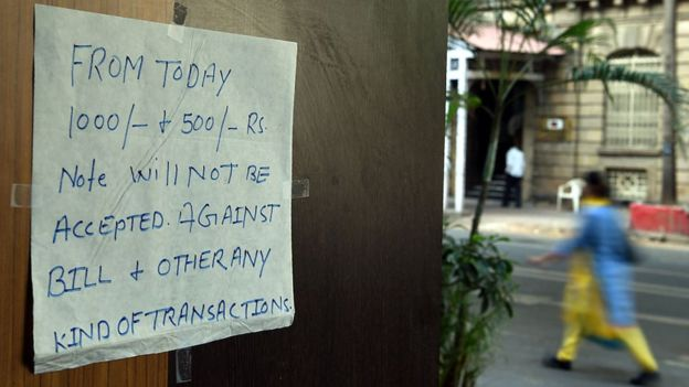 A notice regarding discontinued 500 and 1,000 rupee notes is posted at the entrance of a restaurant in Mumbai