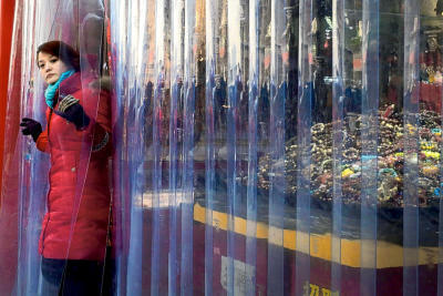A salesperson looks out of her fashion accessories shop near Qianmen Street, a popular tourist spot, in Beijing on Jan. 20. (AP Photo/Andy Wong, File)