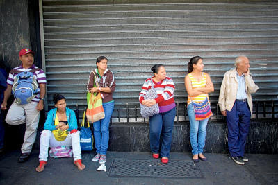 People wait in line to buy groceries at government regulated prices in Caracas, Venezuela, on Jan. 27. (AP Photo/Ariana Cubillos, File)
