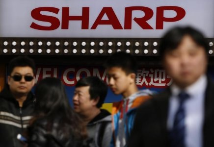 A logo of Sharp Corp is seen above Chinese tourists standing outside an electronics retail store in Tokyo, Japan, February 26, 2016.  REUTERS/Yuya Shino