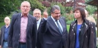 Sigmar Gabriel, surrounded by people, flicking his middle finger in the direction of the camera